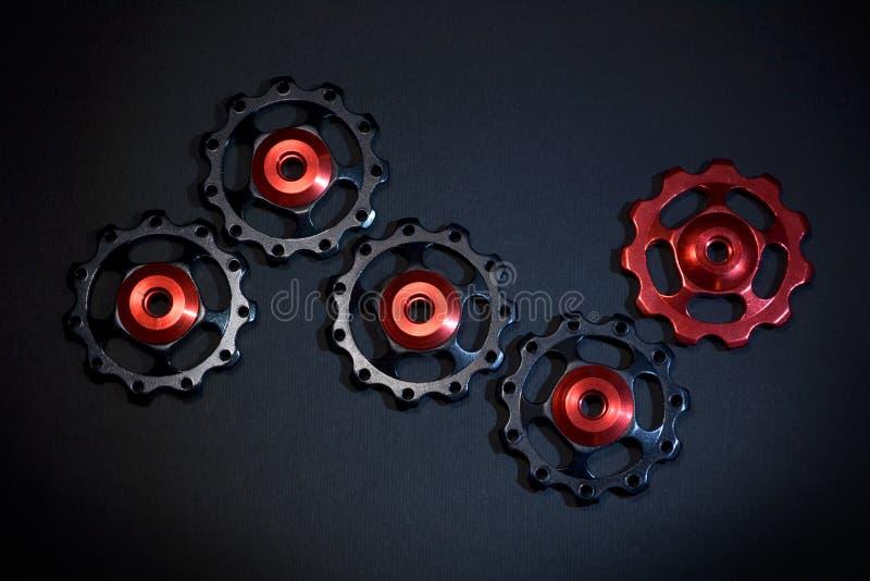 De kleurenrollen, zwarte, rode toestellen voor fiets brengen derailleur op zwarte achtergrond groot stock afbeeldingen
