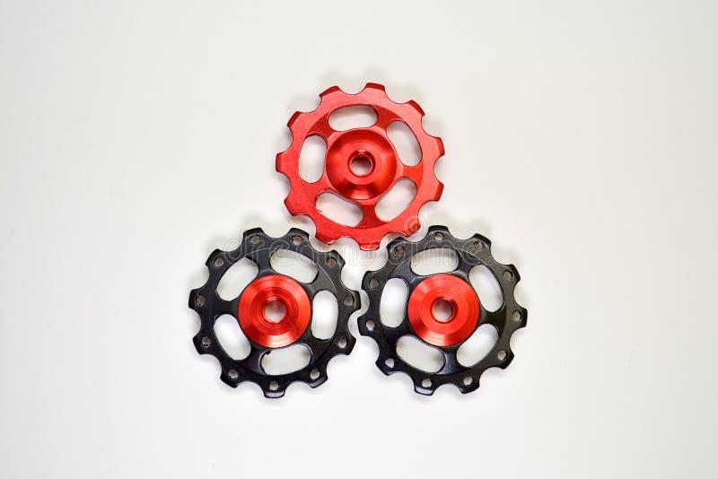 De kleurenrollen, zwarte, rode toestellen voor fiets brengen derailleur op een witte achtergrond in vorm van driehoek, met copysp royalty-vrije stock foto
