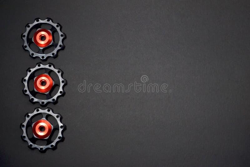 De kleurenrollen, zwarte, rode toestellen voor fiets brengen derailleur op grijze achtergrond in linkerkant, met copyspace groot stock afbeelding