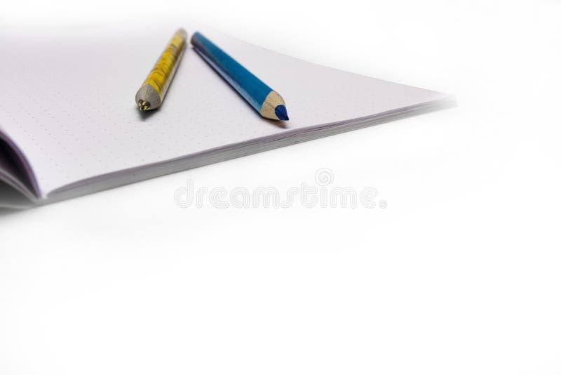 De kleurpotloden zijn op het schoolnotitieboekje Het notitieboekje ligt op het Bureau op school de jonge geitjes leren stock foto