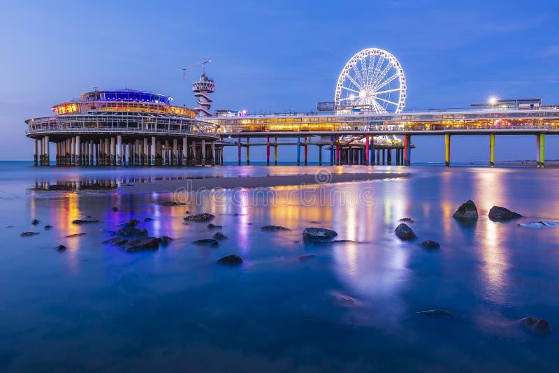 De kleurrijke blauwe uurzonsondergang op kustlijn, het strand, de pijler en ferris rijden, Scheveningen, Den Haag royalty-vrije stock foto