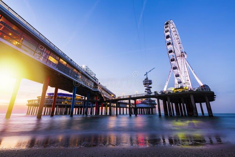 De kleurrijke blauwe uurzonsondergang op kustlijn, het strand, de pijler en ferris rijden, Scheveningen, Den Haag stock fotografie