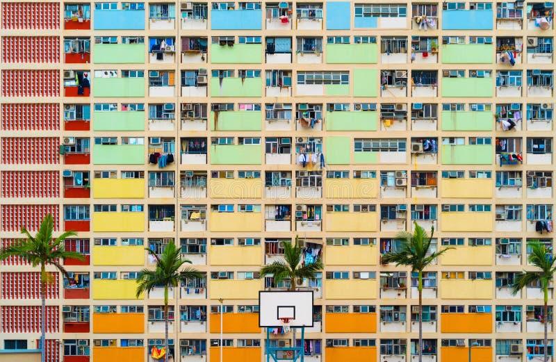 De kleurrijke bouw van de regenboogpastelkleur met van de basketbalhof en voorgevel venstersachtergrond Architectuur de bouwontwe stock foto's