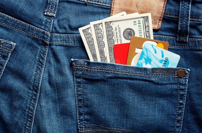 De kleurrijke creditcards en 100 dollar rekeningen in een blauwe rug van Jean in eigen zak steken stock foto