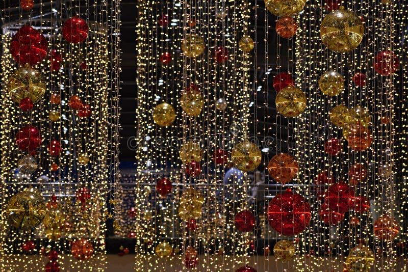 De kleurrijke decoratie van Kerstmis De wintervakantie en traditionele ornamenten op een Kerstboom Verlichtingsketens - kaarsen v stock fotografie
