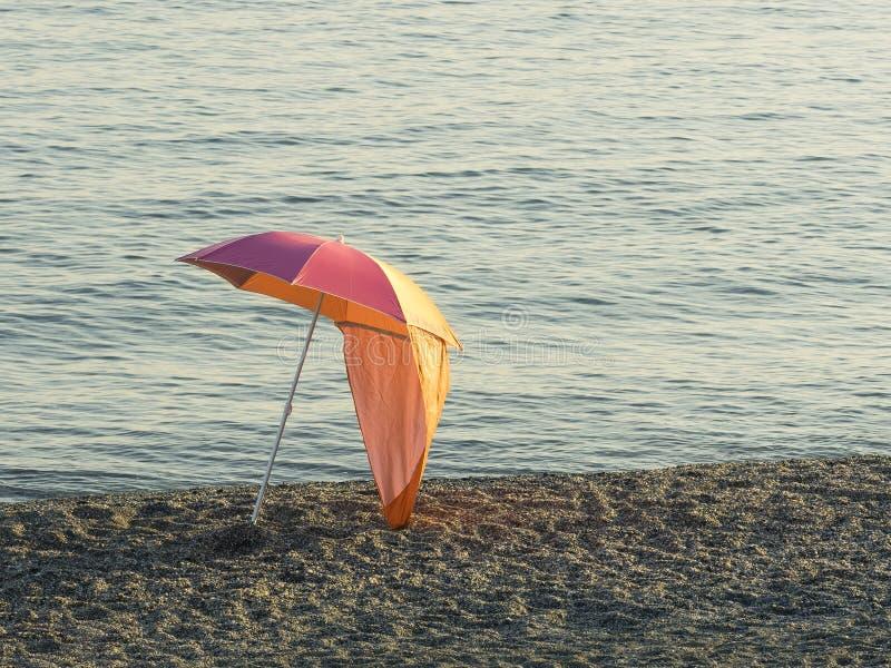 De kleurrijke die paraplu van het parasolstrand op een kiezelsteenstrand bij zonsondergang wordt geïsoleerd royalty-vrije stock afbeeldingen