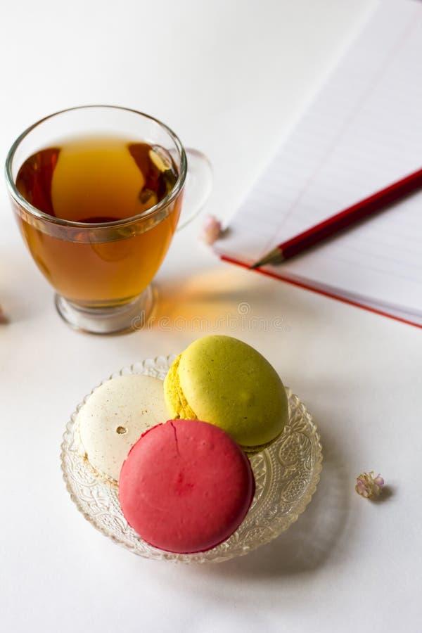 De kleurrijke Franse makarons met kop thee op de witte vlakte lagen stock foto