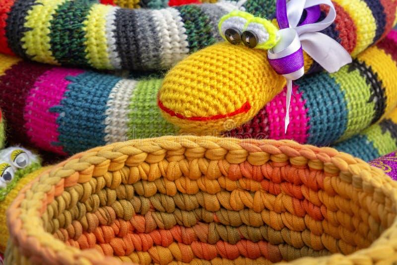 De kleurrijke gehaakte met de hand gemaakte speelgoedslang en de mand voor verkoop in een herinnering winkelen op de markt royalty-vrije stock afbeeldingen