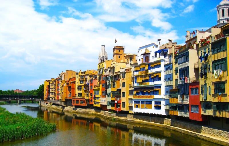 De kleurrijke gele en oranje huizen wezen in waterrivier, in Girona, op Catalonië spanje Kerk Heilige Mary Cathedral bij achtergr royalty-vrije stock foto