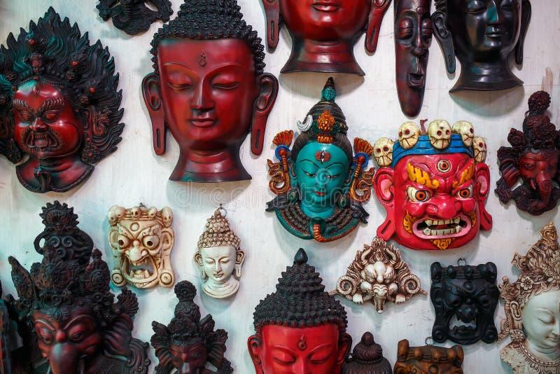 De kleurrijke gesneden maskers worden verkocht, hangen de gekleurde maskers van verschillende parfums op de muur stock foto