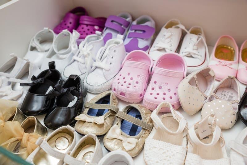 De kleurrijke gloednieuwe schoenen van het babymeisje binnen kast stock foto