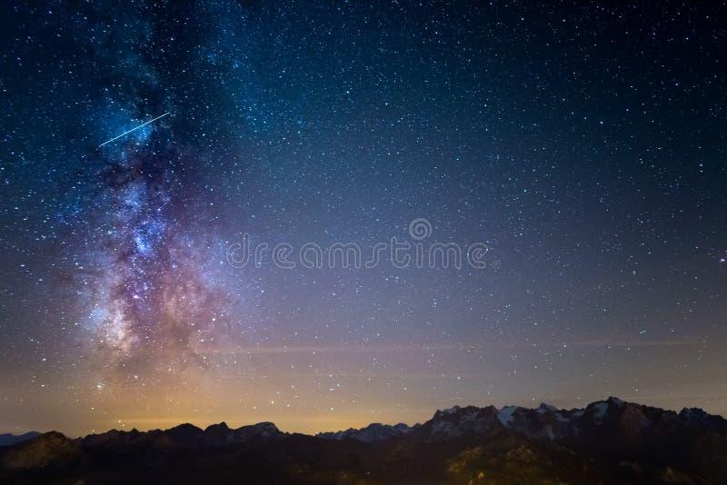 De kleurrijke gloeiende Melkweg en de sterrige hemel over de Franse Alpen en majestueuze Massif des Ecrins stock foto