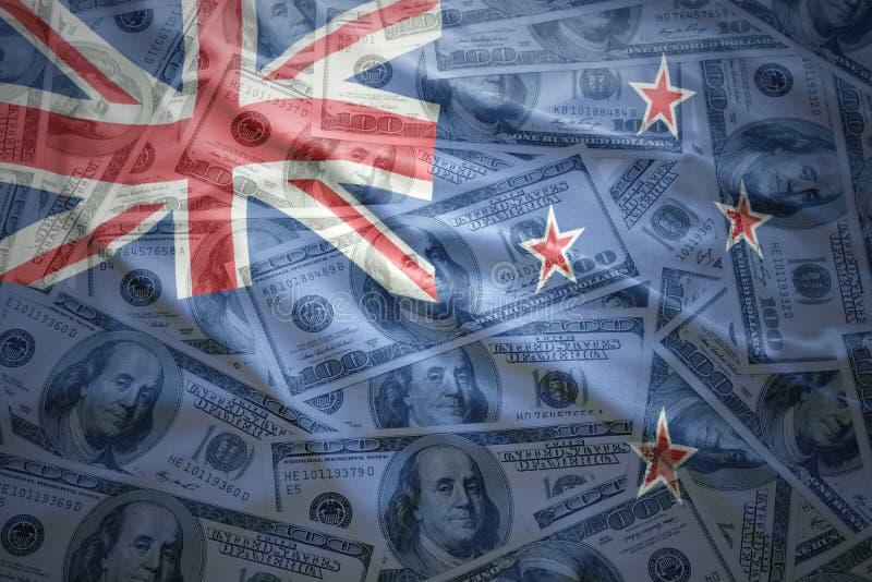 De kleurrijke golvende vlag van Nieuw Zeeland op een achtergrond van het dollargeld stock afbeelding
