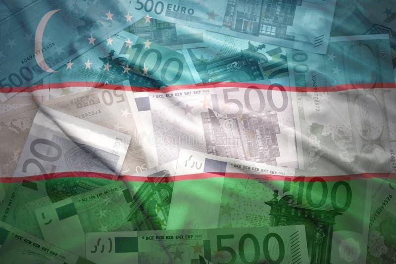 De kleurrijke golvende vlag van Oezbekistan op een euro achtergrond stock foto