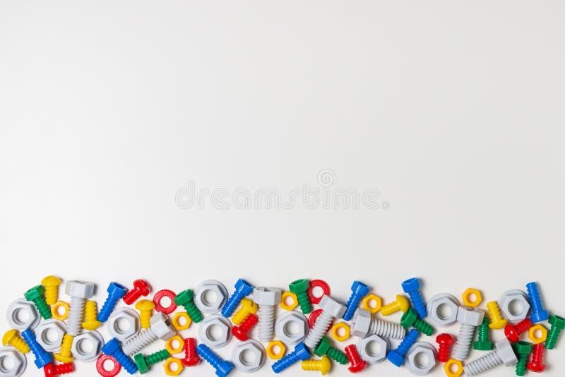 De kleurrijke grens van het jonge geitjesspeelgoed Plastic stuk speelgoed hulpmiddelen, bouten en noten op witte achtergrond Hoog royalty-vrije stock fotografie