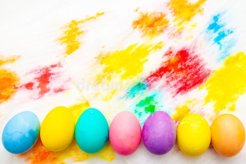 De kleurrijke grens van het paaseierenkader op veelkleurige geschilderde achtergrond Hoogste mening, Copyspace royalty-vrije stock foto's