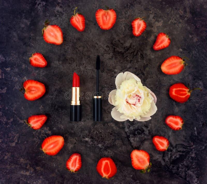 De kleurrijke heldere samenstelling van maakt toebehoren, omhoog aardbeien en pioenbloem Vlak leg, hoogste mening royalty-vrije stock foto's