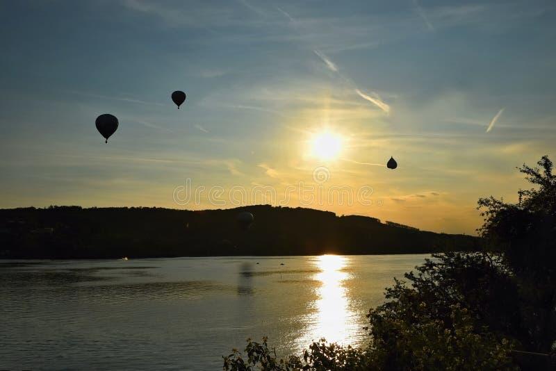 De kleurrijke hete luchtballon vliegt bij zonsondergang Brno Dam - Tsjechische Republiek stock foto