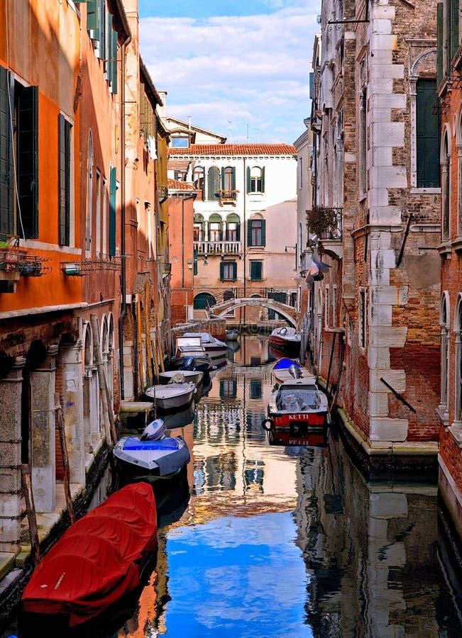 De kleurrijke hoeken van Venetië, oude gebouwen en vensters, waterkanaal met bezinningen, boten en kleine brug, Italië stock afbeelding