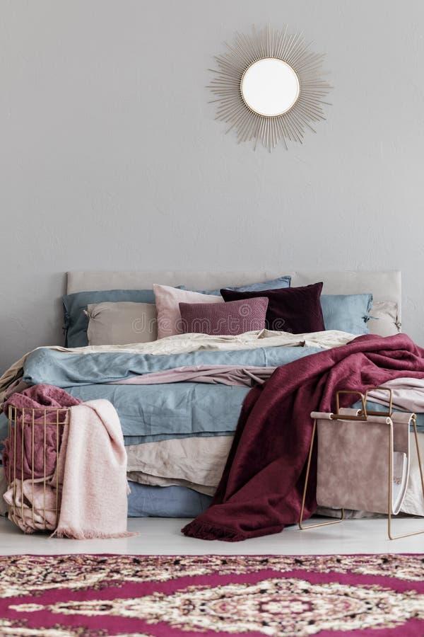 De kleurrijke hoofdkussens en deken van Bourgondië op comfortabel bed in modieus slaapkamerbinnenland royalty-vrije stock afbeeldingen