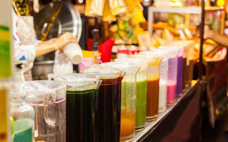 De kleurrijke Koude Thaise Thee van het Melkijs in kruiken op de marktkraam van het straatvoedsel Traditionele Thaise die Drank m royalty-vrije stock afbeeldingen