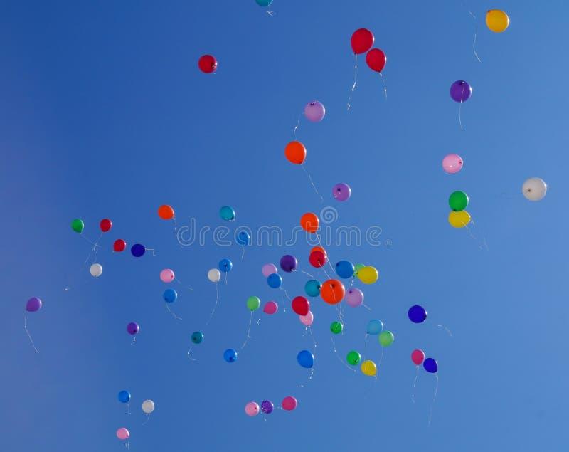 De kleurrijke multicolored opblaasbare ballen vliegen in lucht tegen blauwe hemel als achtergrond tijdens feestelijk festival royalty-vrije stock foto's