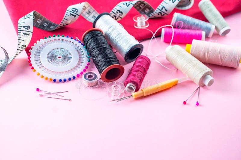 De kleurrijke naaiende draden op een roze achtergrond, leggen boven vlak stock afbeeldingen