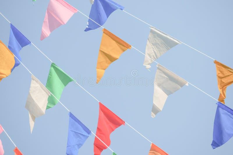 De kleurrijke Partij markeert bunting het hangen op blauwe hemel voor vakantiedecoratie stock foto's