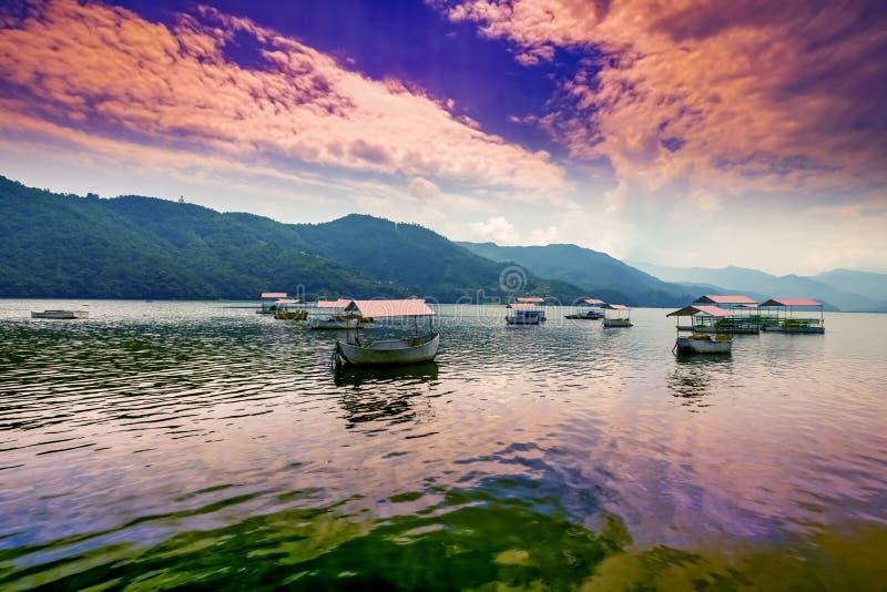 De kleurrijke Pedaalboten die in Phewa-Meer, blauwe heuvels en zonsondergang worden geparkeerd betrekt op achtergrond royalty-vrije stock foto's