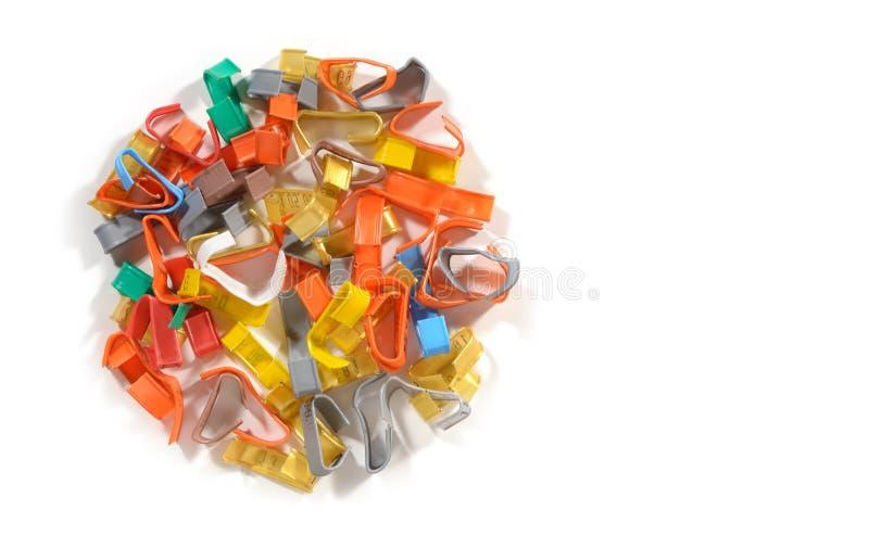 De kleurrijke plastic banden van de metaaldraai pell-mell op witte achtergrond stock fotografie