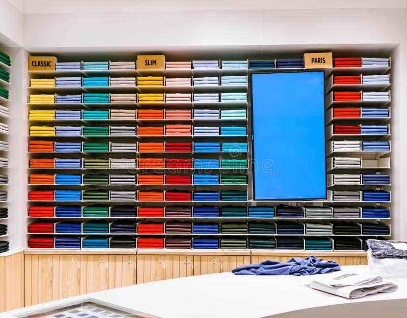 De kleurrijke regenboog kleedt achtergrond Diverse trillende kleurenoverhemden die volkomen op een plank in de winkel worden gevo stock foto's