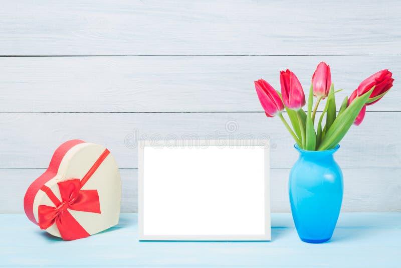 De kleurrijke de rode lentetulp bloeit in aardige blauwe vaas en leeg fotokader met decoratief hart giftbox op lichte houten acht stock foto's