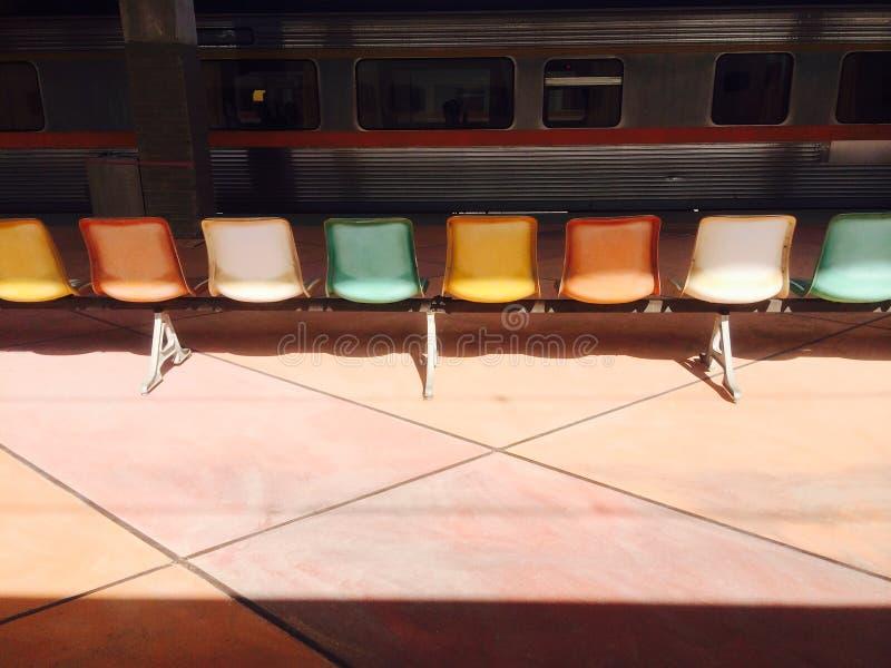 De kleurrijke stoelen zijn op het platform stock fotografie