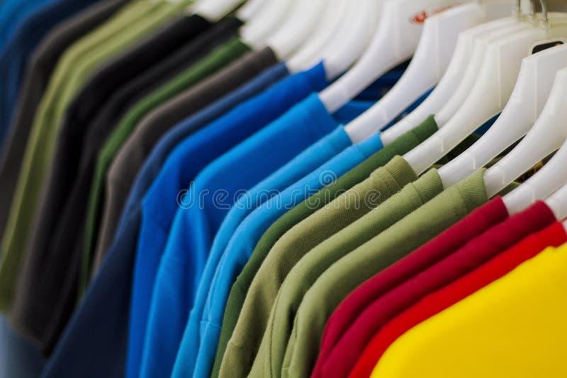 De kleurrijke t-shirts hangen voor verkoop in winkel Multicolored de zomerbovenkant op hanger stock foto