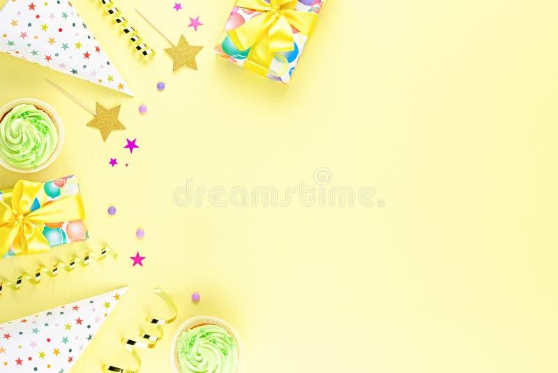 De kleurrijke toebehoren van de verjaardagspartij op geel Verpakte giften, confettien, ballons, partijhoeden, decoratie, exemplaa royalty-vrije stock foto's