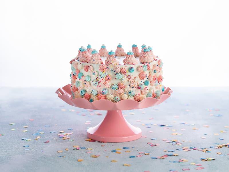 De kleurrijke Verjaardagscake met bestrooit over Witte Achtergrond Het concept van de de verjaardagspartij van vieringschilds royalty-vrije stock foto