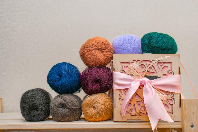 De kleurrijke verschillende ballen van de textielgarendraad Rij van lange brede gevouwen wol op het gebied van de dieptedoos Hout stock afbeeldingen