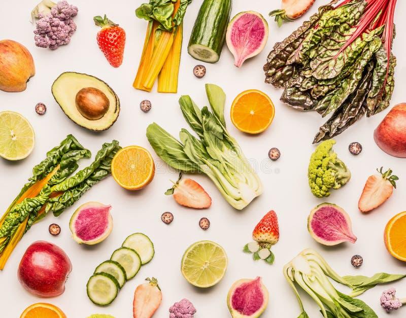De kleurrijke vruchten en groentenvlakte legt achtergrond met de helft sinaasappelen, avocado, citrusvrucht, appelen en bessen, h royalty-vrije stock foto