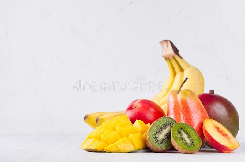De kleurrijke vruchten mengen - gehele vruchten en sappige gesneden plakken - mango, banaan, peer, perzik, kiwi, nectarine op wit royalty-vrije stock fotografie