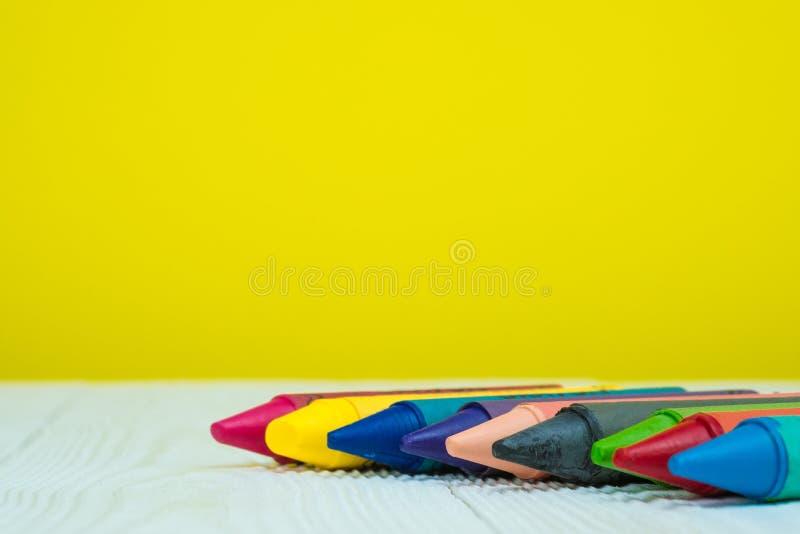 De kleurrijke was schetst potloden op witte houten lijst met exemplaarruimte voor toevoegt tekst stock afbeelding