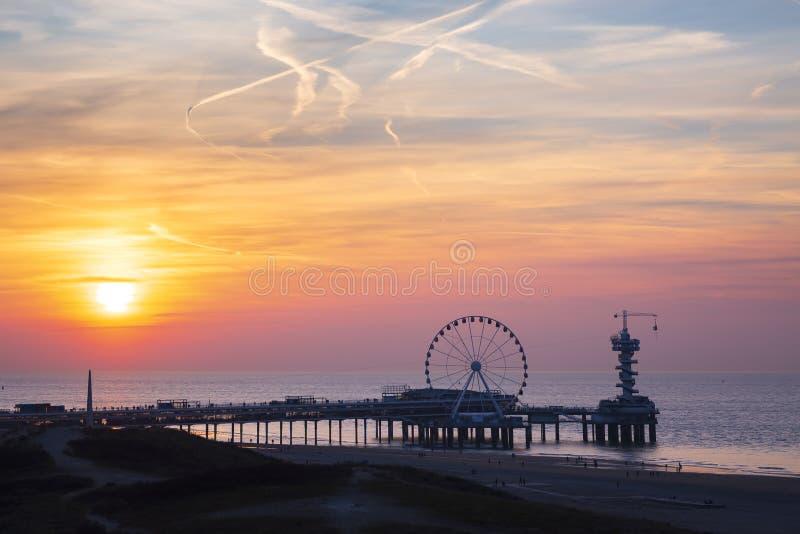 De kleurrijke zonsondergang op kustlijn, het strand, de pijler en ferris rijden, Scheveningen, Den Haag stock afbeelding