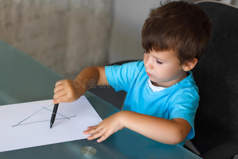 De kleuterjongen leert het schrijven brieven stock fotografie