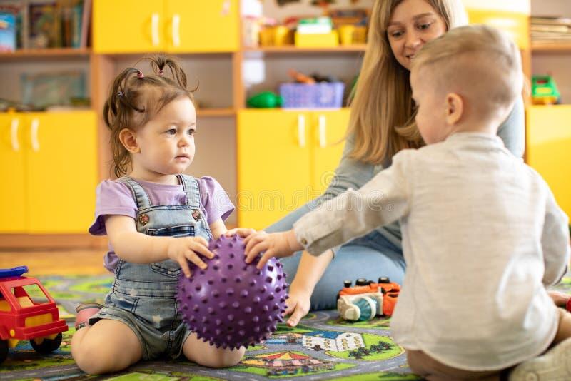 De kleuterschoolkinderen wedijveren met elkaar voor stuk speelgoed bal royalty-vrije stock afbeeldingen