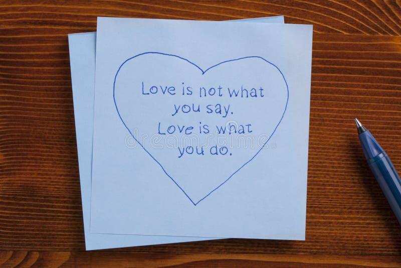 De kleverige nota met tekstliefde is niet wat u zegt De liefde is wat u royalty-vrije stock fotografie