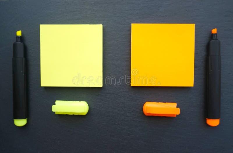 De kleverige nota's in gele en oranje kleur met markeerstiften in hetzelfde kleuren op de zwarte raadsachtergrond royalty-vrije stock fotografie