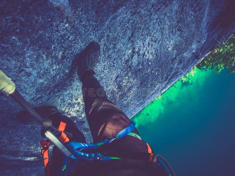 De klimmer bekijkt neer het beklimmen op een steile muur, via ferrata royalty-vrije stock afbeeldingen