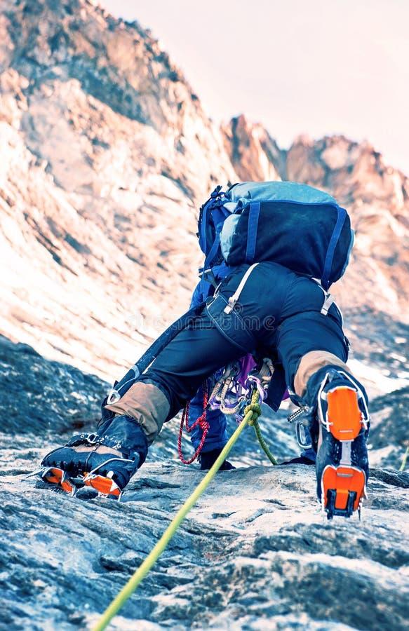 De klimmer bereikt de top van bergpiek Het beklimmen en mounta stock foto