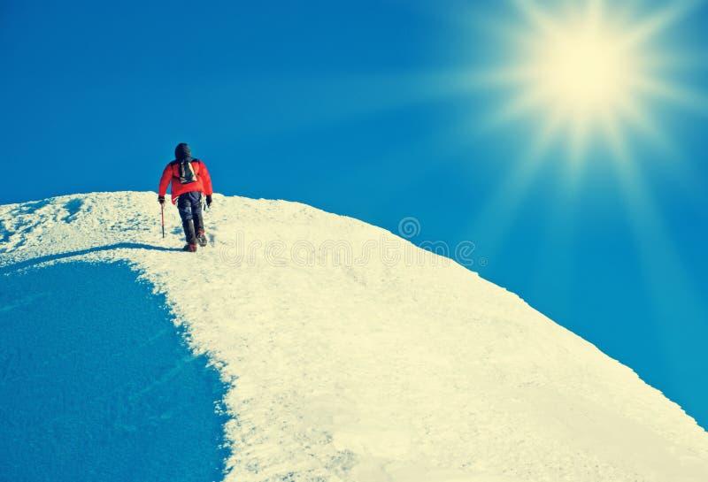 De klimmer bereikt de top van bergpiek Succes, vrijheid a royalty-vrije stock afbeeldingen