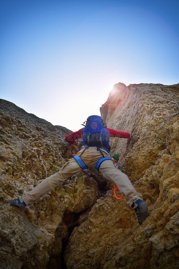 De klimmer die van de rots zich aan een klip vastklampt stock foto's