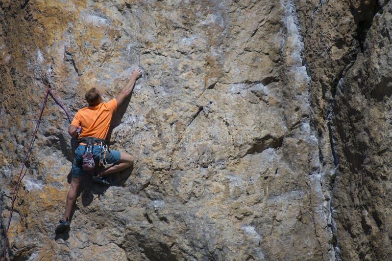 De klimmer die van de rots zich aan een klip vastklampt stock foto